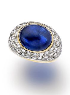 A sapphire and diamond ring, Tiffany & Co. set with a cabochon sapphire, measuring approximately 13.00 x 10.20mm., within a pavé-set bombé surround and polished gold mount; signed Tiffany for Tiffany & Co., with signed box; estimated total diamond weight: 2.00 carats; mounted in eighteen karat gold and platinum