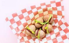 Je kan je paaseieren gewoon even kleuren in wat water met rode uien, of je kan je paaseieren omtoveren in hilarische pareltjes. Wij kiezen dit jaar voor het tweede met de hamburgerpaaseitjes van Studio DIY.