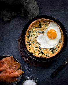 3. Valmista seuraavaksi pannaritaikina. Mittaa munat tehosekoittimeen ja anna niiden vaahtoutua kunnolla. Lisää maito ohuena nauhana ja lisää lopuksi jauhot, maizena sekä ripaus suolaa. Kaada seos kulhoon ja lisää hienonnetut, ryöpätyt nokkoset.  4. Kuumenna valurautapannu (n. 22-24 cm halkaisijaltaan) 200-asteisessa uunissa voinokareen kera, kaada taikina kuumaan pannuun ja kypsäksi n. 20 minuutin ajan.  5. Paista päälle muutama sunny side up -kananmuna ja koristele annos…