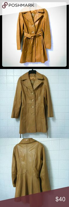 """Tannery Tan LEATHER Coat Size 9/10 Made especially for Montgomery Ward """"The Tannery"""" Has 4 textured buttons on front and belted waist. Two deep front pockets roomy enough for your technology. In very well kept condition. No visible signs of wear Rear of coat has a teeny tiny pin hole where security tag was place. Hard to find and Nearly impossible to see, especially while wearing- hole is too small to see when on.  Measures 16"""" Shoulder to Shoulder 18"""" Armpit to Armpit 22"""" Long Sleeves 31""""…"""