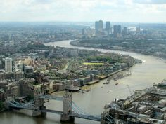 View of London - This brilliant photo which is premiering this travel album shows the amazing buildings, architecture and attractions. This photo was taken at the top of the very tall Shard building which lets photographers take great photos of the great city. Canary Wharf can be seen and also the Tower Bridge.