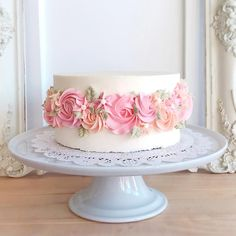 Delicious Home Bakery double-round cake covered in Home Bakery Buttercream Frosting and ringed with hand-piped peach and pink flowers, edible leaves, and singlets. Choose either chocolate or white cake.
