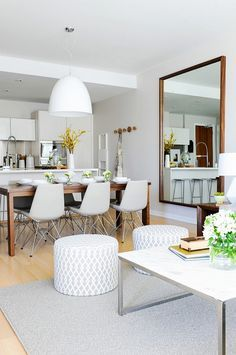 Modern dining space beside kitchen with modern light fixture and large mirror