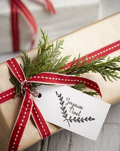 Gift wrapped in brown paper and decorated with a red and white ribbon and a sprig of greenery.