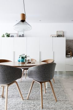 House tour: a light, contemporary apartment in Melbourne: A 'Bronze' dining table by Melbourne designer Daniel Barbera is paired with upholstered 'About a Chair' bucket seats by Hay and a grey, textured rug by Halcyon Lake. A suspended 'Muffins 03B' pendant by Brokis is mirrored by glass domes by Amanda Dziedzic on the table below. Assorted Indian artefacts, reflecting the owners' connection to their heritage, are displayed in copper framed glass boxes.