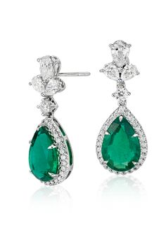 These earrings showcase vibrant pear shape emeralds accented by a beautiful three-stone diamond cluster drop detail set in 18k white gold.