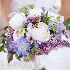 white peony bouquet accented with purple wildflowers.