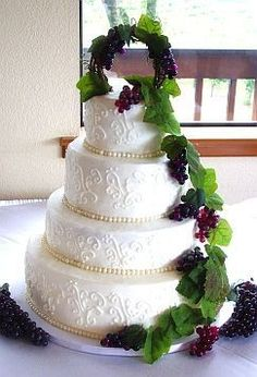 """WASC cake that I added sprinkles to in order to make it a """"funfetti"""" cake at the bride's request. The wedding was at a vineyard so we went with this design. Purchased the fake grapes and leaves at a craft store and made the topper and side arrrangement. Fondant pearls around each tier. TFL!!"""