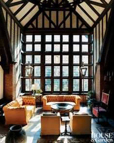 The main sitting area of the Elizabethan-style great hall in a Hamptons, New York, home features a pair of golden chesterfield sofas.