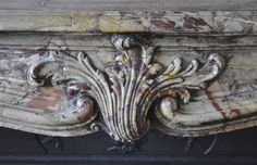 Beautiful antique Louis XV period fireplace in Sarrancolin Ilhet marble decorated with foliated cartouche