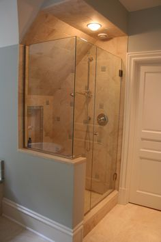 Frameless corner glass shower with slanted ceiling and sand colored tile