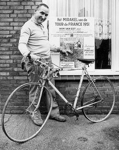 Wim van Est with his old 1951 bike    Willem van Est (25 March 1923 – 1 May 2003) was a Dutch racing cyclist.    He is best known for being the first Dutch cyclist to wear the yellow jersey in the Tour de France of 1951, and for falling into a ravine while wearing it. But his watch (a Pontiac) continued ticking!    He points to the poster where his whole adventure is on.