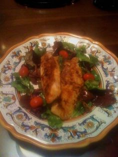 Blackened Tilapia fillets over a bed of green salad garnished with cherry tomatoes.