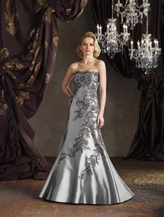 Strapless silk wool shantung modified A-line gown features hand-beaded floral embroidery, sweep train. Matching shawl trimmed with matching embroidery (shown wrapped around shoulders) and removable straps included. Sizes: 4 – 20