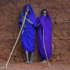 Survival International    The vibrant blue of the young Suri men's robes stands out against a cracked earthen wall in the Omo Valley, Ethiopia (photo: Trevor Cole).