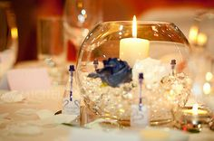 8'' glass fishbowls, half filled with clear gel balls mixed with pearls, candle in centre  with 1 navy blue and 1 cream high quality silk foam rose either side, diamonte centre. comes with 3 tealight holders and a bottle of champagne mini bubbles. With scented candles really make for a romantic dreamy and aromatic centrepiece.