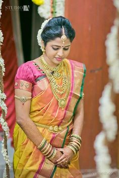 Traditional Southern Indian bride wearing bridal silk saree, jewellery and hairstyle. #IndianBridalMakeup #IndianBridalFashion  Temple jewelry. Yellow silk kanchipuram sari.Braid with fresh flowers. Tamil bride. Telugu bride. Kannada bride. Hindu bride. Malayalee bride.