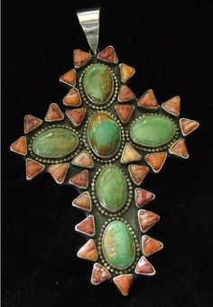 """Beautiful Handmade Sterling Silver Cross from a Private Collection  Made by Navajo Artist """"George Francis""""  Signed """"MGD""""  Cross measures 4 1/4 inches tall (not including the bale) x  3 1/4 inches wide  6 Green Turquoise stones measure 3/4 x 1/2 inch  Turquoise stones are surrounded by hand cut spiney oyster"""