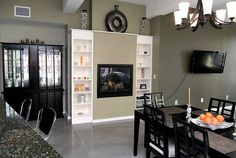 Main living space in a condo with a contemporary and industrial style. Includes a gas fireplace with built-in shelves. Concrete floor, breakfast bar and dining room table.