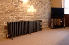 Etonian 6 column cast iron radiators in gun metal in a customer's contemporary styled bedroom