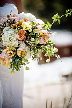 Lauren Brown Photography The beautiful bridal bouquet included David Austin garden roses, hydrangeas, tulips, pieris, ranunculuses, and leafy greenery. Venue: Rainbow Ranch Lodge Bride's Gown: