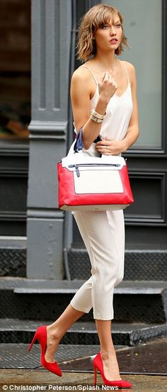 Street chic: Karlie wore a delicate white ensemble and red pumps, as she toted a matching handbag for her editorial shoot