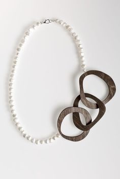 Wood Links and Freshwater Pearl Necklace- Three abstract wooden shapes link together to form a bold chain hanging amidst a strand of freshwater pearls. This asymmetrical necklace is a modern update on the classic pearl necklace.