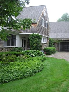 stone + cedar shake + shingle combined with ivy, a weathered shingle and not-so-manicured ground cover. Makes the house look much older