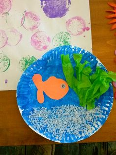 Paper plate fish tank.  rice as sand, green tissue paper seaweed