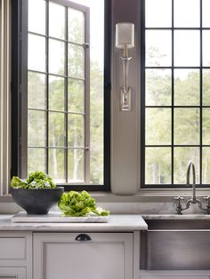 Love the Windows! Kitchen features gray cabinets paired with white marble countertops fitted with a stainless steel apron sink and deck-mount gooseneck faucet and Ruhlmann Single Sconces. Luxury Interior Design, Home Interior, Home Design, Kitchen Interior, Design Ideas, Interior Walls, Design Design, Home Decor Kitchen, New Kitchen