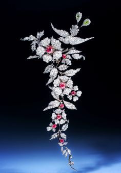 An important 19th century ruby and diamond branch brooch, designed as an articulated foliate spray surmounted by a bird of paradise, set with circular-cut and cushion shaped rubies, circular and rose cut diamons, pear-shaped peridots, mounted in silver and gold. Detaches into four brooches. Probably English, circa 1880.