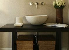 Contemporary zen bathroom design with mushroom grasscloth wallpaper, ebony stained repurposed bathroom washstand, round stone vessel sink, polished chrome wall-mount faucet, wood vase and woven baskets.