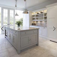 This bright and light shaker style kitchen is painted in bespoke Tom Howley paint colour; Chicory, the light Ivory Spice granite