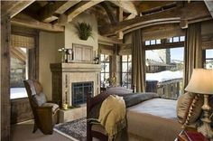 Cozy Country/Rustic Bedroom with fireplace and wood beam ceiling.