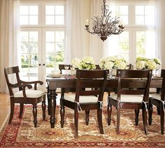 handsome Dining Room Design With Wooden Dining Table And Wooden Chairs Also Antique Cabdlelier And Flower With Patterned Carpet And White Curtain Also Glass Door