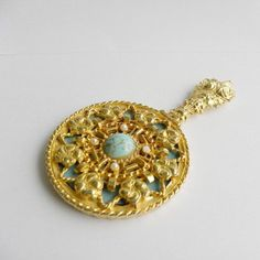 1960s vintage hand held compact mirror by Mirella Adored with faux turquoise and pearl cabochon with a very ornate gold decoration Signed Mirella