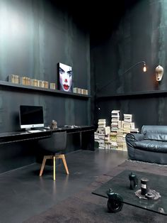 SUPER BLACK OFFICE SPACE. GENEROUS CEILING HEIGHT. FULL WIDTH BLACK SHELVING. GLASS COFFEE TABLE WITH OVERSIZED CASTOR WHEELS. LOW SHEEN BLACK WALLS