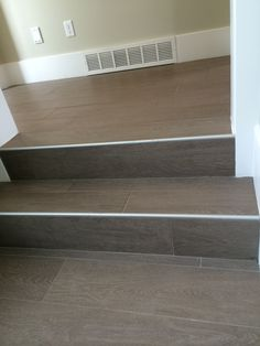 Wood floor tile on stairs with metal end cap - this could be a solution to your stair problem.