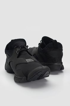 Y-3 Kohna Black Sneakers. Lightweight neoprene all black Y-3 sneakers. Lace-up closure with split rubber sole, striped grosgrain detail at back and logo detail at front. Black suede leather heel tab and black rubber sole. Main body and vamp in mesh textile. Sidewall in matte elastane. Tongue, heel and heel collar in leather. Heel strap in webbing. Lining: Heel lining in suede, remainder unlined. Neoprene sockliner. EVA midsole for cushioning. Rubber outsole. Upper: 90% Neoprene 10% Leather…