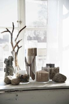 Instant beach. Clear glass hurricanes showcase sand, beach pebbles and driftwood for an instant beach.