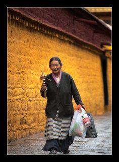 a woman with a prayer wheel - Lhasa, Tibet
