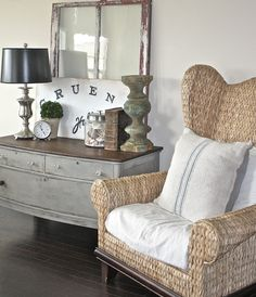 a gray dresser and wicker armchair create a cozy reading corner in a bedroom