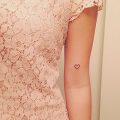 Tiny heart tattoos on each arm with 'H' and 'I' in them