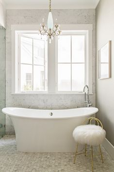 Bathroom with a large freestanding tub, a small fur stool, and a chandelier