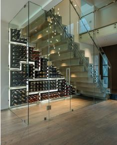 Under Stair wine room with custom glass featuring the PEG System wine racking on glossy black finish backings. The cut out panels form a mosaic pattern with halo lighting for added dramatic effect. Wine Cellar Modern, Glass Wine Cellar, Home Wine Cellars, Wine Cellar Design, Under Stairs Wine Cellar, Wine Cellar Basement, Wine Wall, Wine Rack Wall, Wine Racks