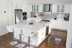 Glossy White Kitchen Cabinets + white countertop + wood floor