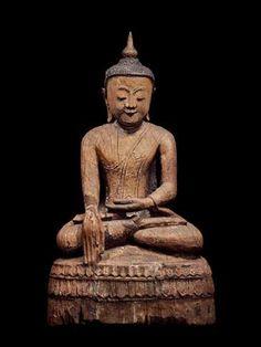 Bouddha assis en bhumisparça-mudrâ. En bois érodé à traces de laque de couleur brune. Birmanie, XVIIIe s. H : 85 cm L : 46 cm P : 30 cm
