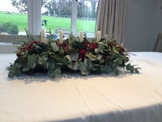My take on an advent arrangement, I used red roses and carnations, brunia, Eucalyptus, Mimosa,  Ivy leaves and wax flowers