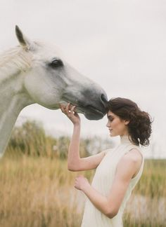 .A girl in a white dress takes a photo with a white horse in a field.