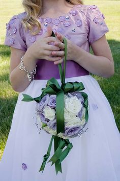 The flower girl forgoes a basket for a pomander of purple and white roses tied with emerald satin ribbons.